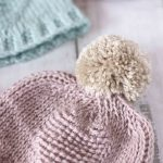 Afghan Crochet Baby Hat Up Close Image. Partial Hat In Blue And Main Image In Pink. Large Pom Pom.    thecrochetspace.com