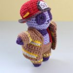 Amigurumi Panda Firefighter Freddie.Side view of lilac/ purple colored panda, wearing pants jacket and red helmet    thecrochetspace.com