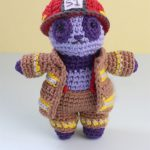 Amigurumi Panda Firefighter Freddie. Front view of lilac/ purple colored panda, wearing pants, open jacket and red helmet    thecrochetspace.com