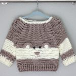 Baby Bear Crochet Sweater on a hanger. Front view. Sweater in brown and cream with added bear face || thecrochetspacecom