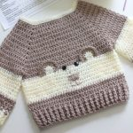 Baby Bear Crochet Sweater. Cream and Brown sweater at anangle. Charming Bear face on front || thecrochetspace.com
