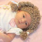Cabbage Patch Crochet Hat. Baby laying with wig on || thecrochetspace.com