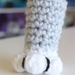 Large Close Up Of One Crochet Cat Paw Sock In Grey And White Shown On One Chair Foot || therochetspace.com