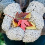 180 Minutes Crochet Mittens. two hans wearing mittens holding Autumn leaves || thecrochetspace.com