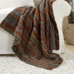Creeping Crochet Cluster Afghan. Afghan thrown over sofa crafted in autumnal tones || thecrochetspace.com