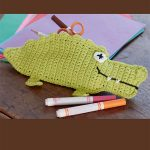 Crochet Alligator Pencil Case. Green gator surrounded by pens    thecrochetspace.com
