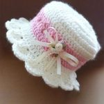 Crochet Baby High Hat. White crocheted hat with pink band above scalloped brim. Pale pink ribbon laced through band accent ribbon bow || thecrochetspace.com