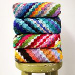 Crochet C2C Yarn Buster . Stack of 4x blankets, folded and put on a wooden stool || thecrochetspace.com