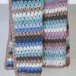 Crochet Cozy Baby Blanket. Image of two baby blankets on different shelves. One in pinks and one in blues || thecrochetspace.com