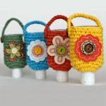 Crochet-Hand-Sanitizer-Cozy. Row of 4 bottles of hand sanitizer in different colored crochet covers and with flower on front Thecrochetspace.com