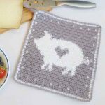 Crochet Pig Hot Pad. White pig with greay love heart in the center and on a grey background || thecrochetspace.com