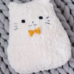 Crochet Plush Pussy Pillow . White fur cat on grey crocheted afghan    thecrochetspace.com
