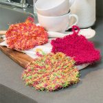 Crochet Scalloped Edge Scrubby. Three scrubbies in different colors in the kitchen || thecrochetspace.com