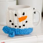 Crochet Snowman Mug Hug . Crafted in white with snowman face and blue scarf || thecrochetspace.com