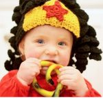 Crochet Wonder Woman Wig. Little girl in full black spiral crochet hair wig with added yellow crown and red star. Front view image    thecrochetspace.com