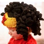 Crochet Wonder Woman Wig. Little girl in full black spiral crochet hair wig with added yellow crown and red star. Side view    thecrochetspace.com