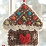 Crocheted Gingerbread Pot Holders. One gingerbread house with red heart, white edging and muli colored accents || thecrochetspace.com