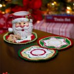 Crocheted Party Doily Coasters. Coasters crafted in red, white and green, with a Christmas Santa mug on top of one || thecrochetspace.com