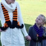 Crocheted Witches Legs Scarf. Mother and daugher wearing a scarf each. One in purple and black and the other in orange and black || thecrochetspace.com