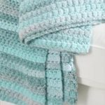 Easy Aston Crochet Throw. Close up image of throw on sofa. Different blues || thecrochetspace.com