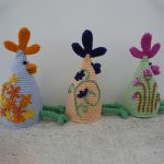 Easy Crochet Chicken Run. Three chickens sitting in a row. Blue, yellow and green. All with thin legs outstretched || thecrochetspace.com