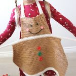 Easy Crochet Gingerbread Apron. Little girl about to tie apron || thecrochetspace.com