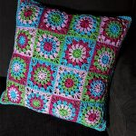 Easy Crochet Granny Pillow against black backdrop. Beautiful image of 16 Granny Squares with a Crab Stitch Edging in Pinks, blue and green || thecrochetspace.com
