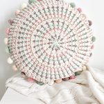 Easy Crochet Mandala Pillow Crafted In Pastel Colors. The Pillow Is Round With Different Pastel Colored Poms Poms Running Around The Edge || Thecrochetspace.com