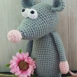 Easy Crochet Ronny Rat. CRafted in dark grey and holding a pink flower || thecrochetspace.com