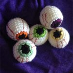 Easy Halloween Crochet Eyeballs. Five eyeballs sitting on a purple cloth || thecrochetspace.com