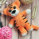 Easy Mini Crochet Tiger. 1x tiger laying next to a pink ball of yarn || thecrochetspace.com