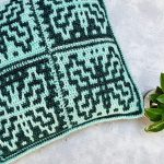 Easy Mosaic Crochet Pillow. Green and black in color. Pictured at an angle. Square pillow || thecrochetspace.com