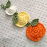 FallingPumpkin Crochet Hanging. Three different colored pumpkins, joined by a green stem and laid on a table | thecrochetspace.com