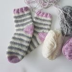 Adult Summer Crochet Socks. Heel and tow in dark lilac and main sock crocheted in grey and white stripes. Dark lilac rib at top. One pair of adult socks with yarn || thecrochetspace.com