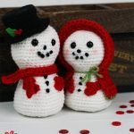 Festive Amigurumi Snowman Couple. Man with black hat and red scarf and woman with red cape    thecrochetspace.com
