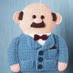 Gents Crochet Belt Holder. Elderly gentleman with balding hair and a mustache in a blue country jacket and brown bow tie. Belts hang from below his jacket || thecrochetspace.com