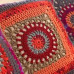 Granny Circle Crochet Pillow. Image mainly of one pillow in hue's of orange and neutral. One large granny square || thecrochetspace.com