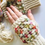 Granny Fingerless Crochet Mitts. One hand in a mitt resting on the other empty mitt. Pastal Colors to match boot cuff set || thecrochetspace.com