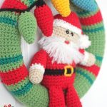 Hanging Santa Crochet Wreath. Santa sitting in the middle of the wreath    thecrochetspace.com
