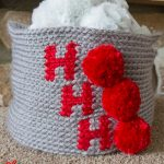 Holiday Ho Crochet Basket. Crafted in grey with red writing and red pom poms || thecrochetspace.com