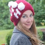 Holiday Ho Crochet Beanie. Lady wearing beanie. Crafted in red with white writing and white pom poms || thecrochetspace.com