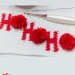 Holiday Ho Crochet Cozy. Image of laid, flat mug cozy in white with red wording and red pom poms || thecrochetspace.com