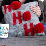 Holiday Ho Crochet Pillow. Crafted in grey with red lettering and red pom poms || thecrochetspace.com