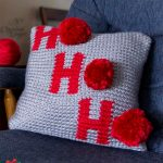 Holiday Ho Crochet Pillow. Positioned on a dark grey chair. Crafted in light grey and red. || thecrochetspace.com