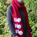 Holiday Ho Crochet Scarf. Red scarf with white writing and white pom poms    thecrochetspace.com