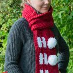 Holiday Ho Crochet Scarf. Close up of scarf. Ho Ho Ho written in white with white pom poms || thecrochetspace.com