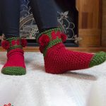 Holiday Ho Crochet Socks. Image of socks with weight on the back, left, foot. Crafted in green and red with red pom poms || thecrochetspace.com