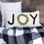 Holiday Joy Crochet Pillow. Cream pillow laying on a black & white plaid blanket    thecrochetspace.com
