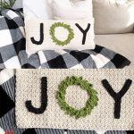 Holiday Joy Crochet Pillow. Two pillow laying on a black & white plaid throw    thecrochetspace.com
