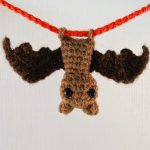 Itsy Bitsy Crochet Bat. Hanging upside-down. Brown body with black wings on a red cord || thecrochetspace.com